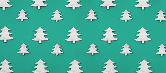 Creative and minimal  Christmas pattern made of wooden christmas trees. Green background. Flat lay top view.
