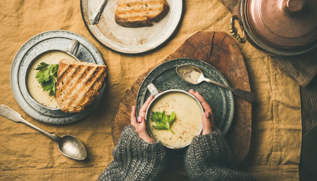 Autumn, Winter home dinner. Flat-lay of Fall warming celery cream soup in cups, grilled bread and female hands over linen tablecloth, top view. Comfort food, vegetarian, healthy and slow food concept