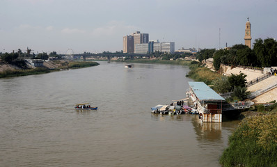 People use a small boat to travel between the banks of the Tigris River in Baghdad