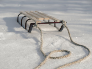 Sledge with rope in snow winter close-up shot. Good background with copy space for winter holidays concept banner.