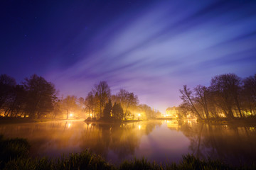 Park in Pszczyna, Poland on a starry night with gentle clouds and stars visible.