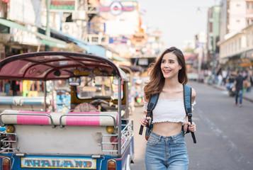 young woman walking the famous backpacker street Khao San in Bangkok, Thailand
