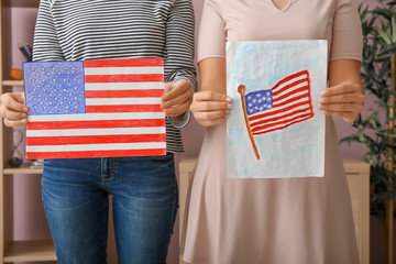 Women holding drawings of American national flag