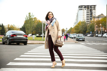 Beautiful fashionable woman crossing road Wall mural