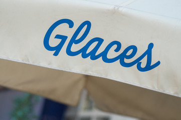 closeup of ice cream store front sign in french text ( glaces, traduction of ice cream)