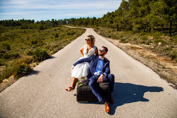 Couple of newlyweds pose with a sofa in the middle of a lonely road