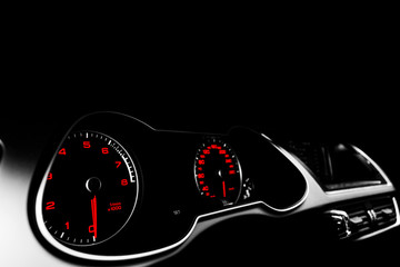 Close up shot of a speedometer in a car. Car dashboard. Dashboard details with indication lamps.Car instrument panel. Dashboard with speedometer, tachometer, odometer. Car detailing. Black and white