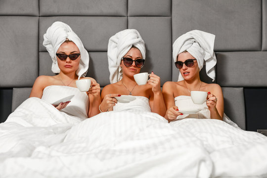 Three slim girls in bed with towels and luxury interior