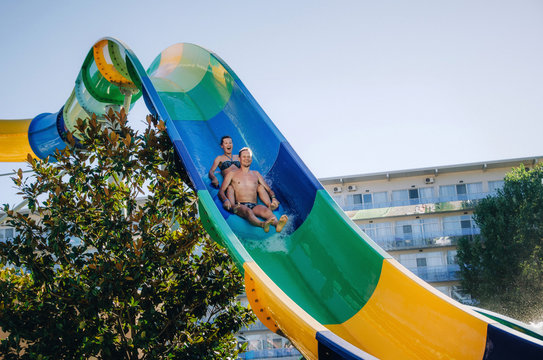 Funny couple taking a fast water ride on a float splashing water. Summer vacation with water park concept.