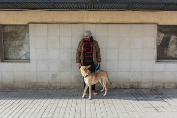 Young man walking, taking care and giving love to his dog