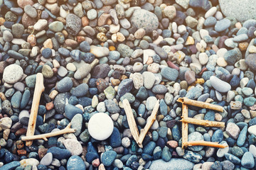 Word love from dry sticks on the sea pebble beach.  Romantic card. Gift by St. Valentine's Day.