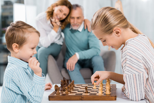 side view of happy kids playing chess while their grandparents sitting near at home