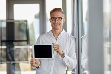 Portrait of smiling businessman showing tablet at the window in office