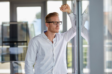 Serious businessman in office looking out of window