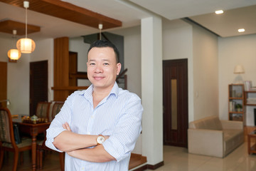Portrait of Asian successful middle aged man standing with arms crossed in his apartment with modern interior