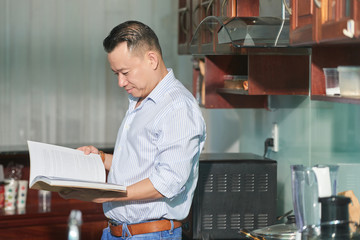 Young man standing in his modern kitchen and looking for the recipe in cookbook