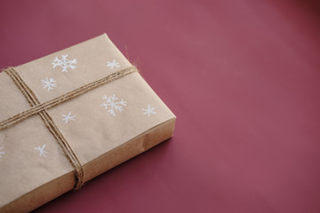 Christmas gift box on burgundy,  marsala color background. Christmas present with handmade decoration. Close up. Copy space