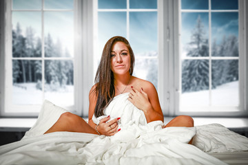 Slim young woman in bed and window background with winter landscape