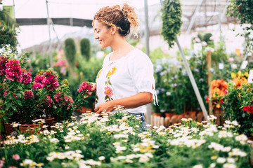 The young woman in a greenhouse with seedlings admires the growth of white flowers like daisies. Concept of care and passion for nature. Shopping and business nature related and easy people lifestyle