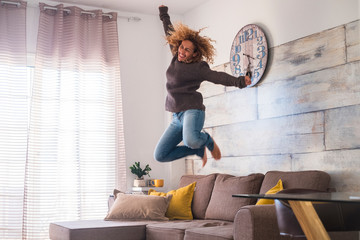 crazy middle age woman jump at home over the sofa to celebrate success - joyful and happiness people concept - craziness and freedom lifestyle for independent modern female