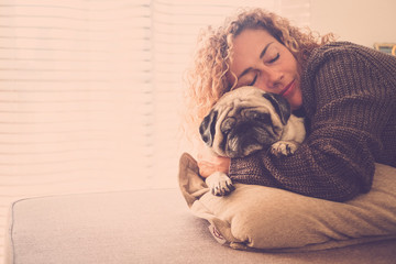 romantic lady hug his best friend old pug on the sofa whiie both sleep together in love and friendship. window light at home - lifestyle and pet therapy concept - warm brown tones autumn style