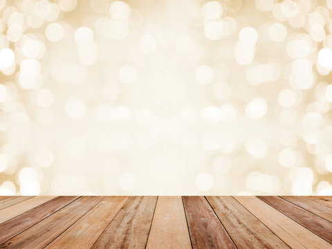 Wood table top over abstract golden background with white bokeh.