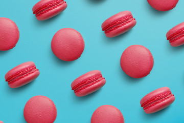 Macaroons on colored background, a pattern of colorful french cookies macarons. Beige, brown french cookies macarons on red background. Gift for Valentine's Day