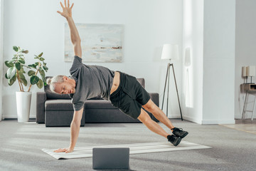 athletic man in sportswear practicing side plank and looking at laptop Wall mural