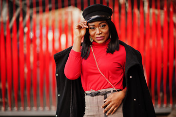 African american fashion girl in coat and newsboy cap posed at street against red background.