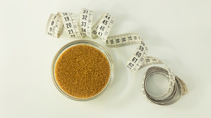 Brown sugar in a small transparent glass bawl and a curled measuring tape in centimeters beside it against a white background. Top view, horizontal perspective, concept idea for nutrition and dieting.