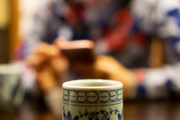 White ceramic cup of Japanese roasted green tea on a table in traditional Japanese restaurant, with young asian woman using smartphone and waiting for her food in the background (The tea is called Hoj