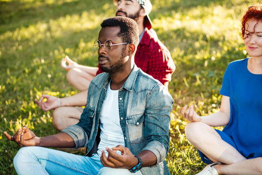 Young african-american man wearing sun glasses, leading a yoga class in public park outdoors. Multiracial friends in casual summer outfit decide to have minutes for meditation while walking in park.