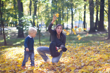 A photographer takes pictures of a child at an autumn photo shoot