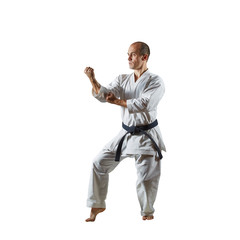 Adult athlete performs formal karate exercises on a white isolated background