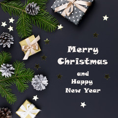 Merry Christmas and Happy New Year greeting card with fir branches, presents, decorations on black