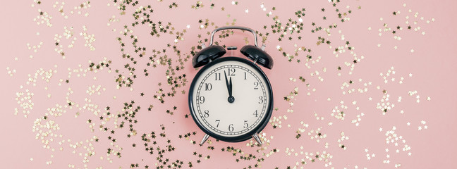 New Year concept. Alarm clock with golden confetti