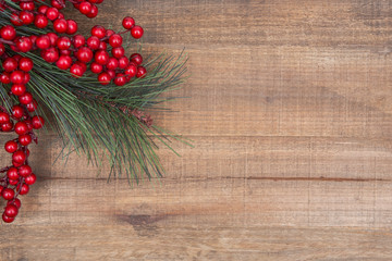 Holiday decoration - pine and berry bush on wooden background.