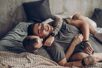 Two sexy blue guys enjoying being together, hugging each other tenderly lying on bed in underwear. Men having happy and cheerful expression. Alternative same-sex Love and Tenderness Concept