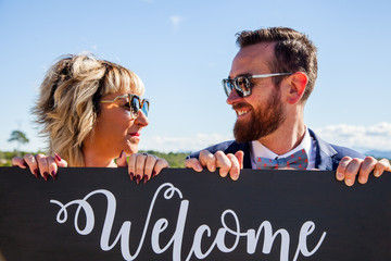 """A man and a woman look at each other and smile over a wooden sign on which the word """"welcome"""" is written."""