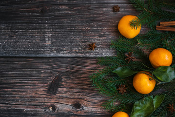 decorative Christmas frame of tangerines, fir branches, cinnamon, star anise. Winter background with copy space. Flat lay top view