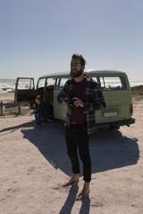 Man holding camera and standing near beach