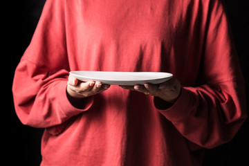 Women hold white plates in their hands.