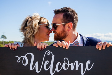 A man and a woman about to kiss over a wooden sign on which he puts the word welcome