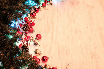 Christmas or New Year background with fir tree branches decorated with cones and red balls on wooden table. Flat lay with copy space