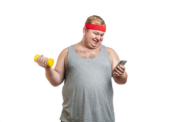 Ironic shot of happy fat man in red hairband exercising with dumbbells and looking at camera isolated on white