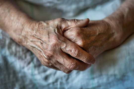 Hands of an old woman folded one over the other. Elderly woman with folded hands. Hands of an old woman close up.