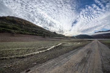 Old road in ruins that is generally flooded by the waters of the reservoir of Riaño in Leon, Spain. In the background you see the mountains between the morning mists.