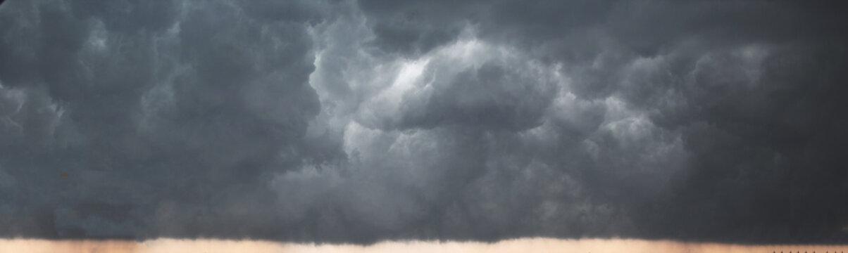 Panorama of cloudy terrifying dark sky before  thunderstorm. Dark dramatic stormy rainy sky.