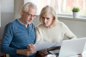 Serious aged husband and wife manage utility bills using laptop at home, concerned senior couple read bank loan or mortgage documents at kitchen table, elder man and woman check insurance paper