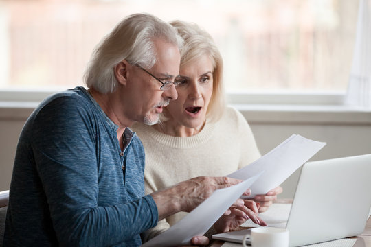 Concerned senior husband and wife hold documents using laptop checking information online, worried aged couple shocked by prices or tax growth reading bills on computer, man and woman have pc problem